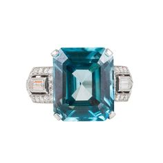 Art Deco Blue Zircon Diamond gold Cocktail Ring. Featuring a beautiful emerald cut blue zircon weighing an estimated 10 carats, this ring also incorporates two bullet shaped diamonds, circled by a diamond trim in an Art Deco style.