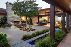 Pockets of water in the concrete courtyard floor break up the landscape and serve as a calming feature. Modern outdoor chairs facing the stacked stone fireplace create an inviting spot for conversation and relaxation.