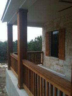 Texas Hill Country stone home with cedar columns, porch railings, and cedar…