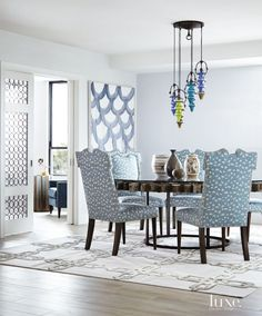 This dining room's round table was designed with an old water mill wheel gear, whose edges echo the lines of the vintage blown-glass pendant lights that hang down in various heights. Kelly Wearstler's Feline fabric for Groundworks covers Kravet chairs.