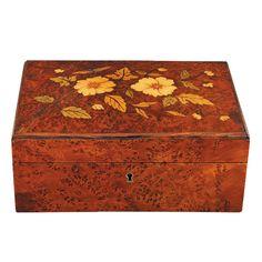 CAJA JOYERO ART-DECÓ Años 20. En madera de tuya con incrustaciones de diferentes maderas frutales y adornos florales. Interior de raso azul y capitoné del mismo color con espejo. Medidas: 9 x 22 x 16 cm.