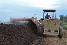 Dan drives the tractor at a snail's pace alongside the linear piles of compost while the paddles of the compost turner aerate the material and re-mound it into nice, neat windrows.
