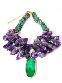 Using genuine Quartz stone along with semiprecious Amethyst beads and Turquoise chips gives this gorgeous pendant necklace a truly luxurious look! Green and gold tones really complement the deep purple. This bold chunky necklace makes a stunning statement piece! Necklace also includes extender chain so as to adjust to desired length. _____________________________________________________ Materials: Pendant - Genuine Quartz. Gemstones - Amethyst and Turquoise stone. Bead Caps - Antique gold...