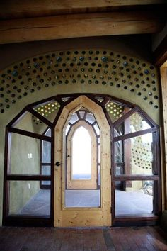 Beautiful archway made with wood and recycled glass bottles! Love Earthship Biotecture!!