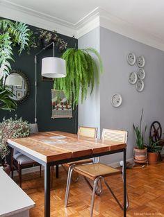 A parede da sala de jantar recebeu pintura com tinta verde escura que se mistura com o verde das plantas.
