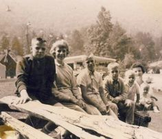 Travelers  Mom and Dad take turns owning the family. There is a companion picture to this one with Dad where Mom is. I like that she is sort of blurry and behind. This seems to be some campground. I like Bill's string tie. The pained look on the boys' faces. A trip with the family. If only we had been more grateful.