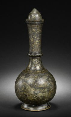 A rare Mughal or Deccani gilt-decorated painted basalt covered Bottle (surahi)   probably Central India, 17th/ 18th Century  of globular form on a spreading foot, with ring to neck rising to gently flared mouth, the lid of domed form, decorated with birds, ibex, and animals in a naturalistic landscape to body and upper neck, a band of simple floral decoration between and to lid