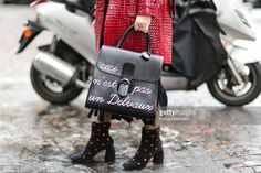 A guest wears sunglasses, a red leather jacket with red fur, a black fringed dress, a Delvaux bag 'Ceci n'est pas un Delvaux', fishnet tights, and black boots with red stars, outside the Veronique Branquinho show, during Paris Fashion Week Womenswear Fall/Winter 2017/2018, on March 6, 2017 in Paris, France.