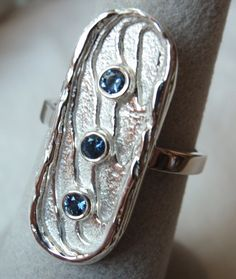 This ring is cast by hand in our shop using cuttlebone and sterling silver, and it is bezel set with 3 natural blue 2.5mm sapphires that weigh 0.18TCW . It is a size 7, but we can size it up or down 1 size for no charge -- there will be a nominal fee for additional sizing.  Cuttlebone is a hard, brittle internal structure found in all members of the cuttlefish. Cuttlefish are marine animals of the same class which also includes squid, octopuses, and nautiluses. Today, cuttlebones are…