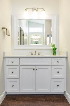 White Shaker cabinets pair with crisp quartz countertops and a white mirror for a clean, fresh design in this timeless bathroom. Wood-look tile floors lend the warmth and appearance of hardwood but boast the durability of porcelain tile.