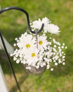 Use shepherd's hooks to hold small arrangements of flowers for aisle decor -- this couple cheery chose daisies and baby's breath!