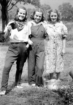 Three cheerful young 1930's lasses in causal garb out working in the garden.