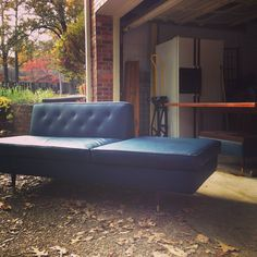 "Navy mid-century divan / sofa in vinyl with brass ""toes"".  Matching ottoman has wooden top."
