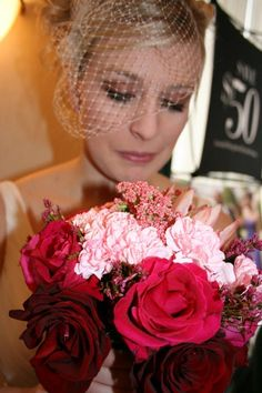 Beautiful bride in a birdcage veil holding a gorgeous pink ombre bouquet