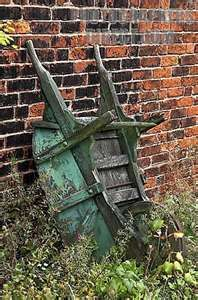 Green wheelbarrow and brick and flowers-Riding around in the wheel barrel while doing yard work when we were kids-Kids are grown-Wheel barrel worn-and bodies are old. No Daddy around to push us anymore. Old and abandoned-Only the memories remain