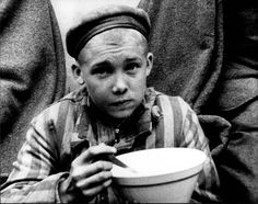 Dachau, Germany, A child wearing a camp uniform, eating his first meal after the liberation.