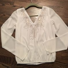 White Blouse This white blouse is from Charlotte Russe. It is a medium. It has rose gold embellishments on the front and a cool cross cross strap pattern on the back. The bottom is gathered. Charlotte Russe Tops Blouses