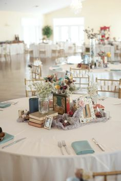 Love this arrangement of vintage books, picture frames and flowers in mason jars #diywedding #weddingcenterpiece #vintage #vintagewedding #weddingdecor