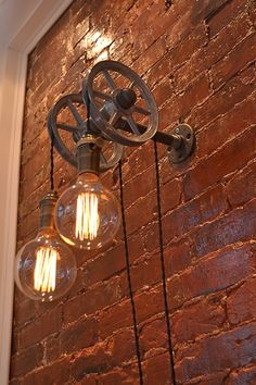 A double pulley wall light with vintage twisted humor wire suspending edison bulbs.