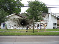 An art installation made to look like the house has a gaping hole going through it.