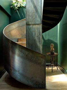 Beautiful metal spiral staircase encased in an Emerald Green hallway.