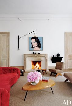In a Paris apartment, over the living room's stone mantel is a silk-screen portrait by Andy Warhol. The stools are by Charlotte Perriand.
