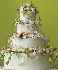 Cake Decorating: Tall tiered White wedding cake with flowers and fruit