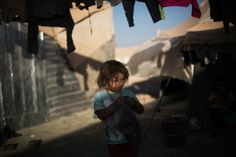 A Syrian girl stands near her family shelter at the Zaatari refugee camp near the Syrian border in Jordan, Oct. 23, 2013.