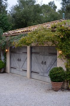 love these garage doors, the aged hinges and pulls, even the gray-blue color. The simple boxwood is just enough although I would use a better pot. Love the clematis and wisteria and the clay roof times, and even the aged finial.