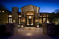 An entry courtyard provides a stunning overture to custom-made iron gates and a spectacular custom-made entry door. The stone facade and beautiful lighting make this entry one of the most inviting in Silverleaf.   Silverleaf Estate Embraces Indoor/Outdoor Living | Drewett Works Architect: C.P. Drewett, AIA, NCARB
