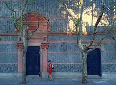Photo of the Day: Between Two Trunks in China   A woman in red is photographed as she passes between two doors and two barren tree trunks in Shanghai, China on September 14, 2015. (Lawrence Wang/Flickr)