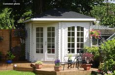 There is only a small amount of timber decking around this white painted Lovat timber summerhouse, but the split level steps and arrangement of pots and chairs adds interest and feature elements. Lovat is available for just £1710 from GardenLife.