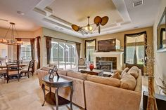 This family room provides a large fireplace, tray ceilings, and a dinette/card table area overlooking the pool, lanai, lake, and golf course in the Wentworth community.