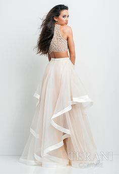 Beautiful 2-piece ensemble featuring a nude, crystal embellished illusion midriff top and sheer, gathered mesh skirt with ribbon accented high-low hemline.
