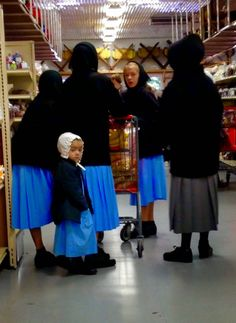 Amish women shopping. Notice one of the women is looking back, as well as a child, but the Amish people DO NOT like to have their pictures taken...