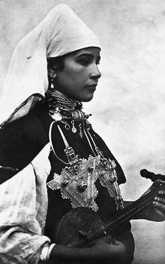 Amazighia musican wearing a haik (but with her face uncovered) and two large fibulae as decorations. From the collection of Si Baaj Abdellah. Women musicians typically played only for women's parties, and groups still exist, mostly around Tetouan, which has a history of very fine female musicians and singers.