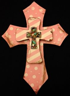"""Small wooden, double layer, wall cross. Covered in pink/white striped and pink/white polka dot scrapbook paper and distressed with brown acrylic paint. The piece is then topped with an ornate silver cross composed of small turquoise pieces, gems and multi-colored beads. Dimensions are approximately 8"""" x 10.5"""". Each cross is handmade with love and truly one of a kind."""