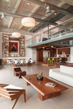 Nahtrang pendant lights and ASA armchairs by Bernardo Senna in living room of Miami loft renovation.: