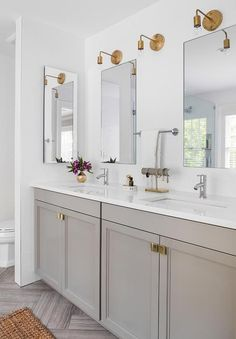 Stunning bathroom boasts a gray dual vanity adorned with brass knobs topped with white quartz fitted with his and hers sinks and inset mirrors lit by brass sconces alongside a gray herringbone tiled floor.