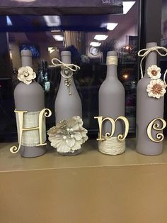 """This wine bottle set features home spelled out, all four wine bottles are refurbished and spray painted and gray/purple color and decorated. These are customizable, and made to order. bottle crafts wedding Items similar to Wine bottle set """"Home"""" on Etsy Recycled Wine Bottles, Wine Bottle Art, Glass Bottle Crafts, Painted Wine Bottles, Diy Bottle, Bottles And Jars, Glass Bottles, Decorated Wine Bottles, Wine Bottle Decorations"""
