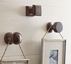 Using antique door knobs or drawer pulls to hang photos....love this!