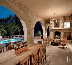 Large arched openings, an iron chandelier from Rose Tarlow and a vintage pub sign over the fireplace from Antique Swan lend English Country style to the pool loggia.