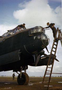 Eod cleaning the front machine guns of Avro Lancaster R5666/`KM-F', while another member of the ground crew cleans the cockpit windows.