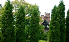 An unusual sight in Ohio: Stan Hywet Hall stands in its Tudor splendor as framed by the pillar shrubs of the Elliptical Garden. ~Wife, Mother, Gardener