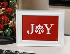 Easy DIY Christmas Decor–Joy Sign Dollar store frame spray painted and printed out or wooden letters. Would be cute to have 'peace' 'love' joy' or other christmassy words!