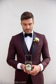 Los angeles outdoor wedding at wayfarers chapel groom burgundy tuxedo with matching vest and black bow tie with white floral boutonniere holding wedding box decor