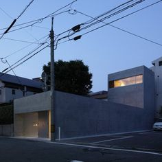 Japanese firm Kazunori Fujimoto Architect & Associates have completed a concrete house in Fukuoka that resembles a half-submerged submarine. House in Ropponmatsu has an L-shaped profile, with the first and second storeys set back so as not to overshadow neighbouring properties. Outward-facing windows were rejected on the ground floor of the bunker-like house in favour of