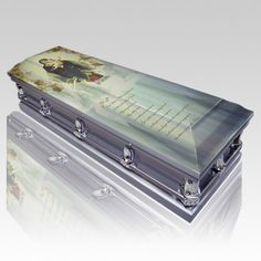 The Ave Maria Casket is made from metal with a wonderful polished to perfection finish. The inside is a grey velvet. The casket is a half-couch design. The interior also includes a matching pillow and throw. The exterior, meanwhile, is decorated with traditional corners, accessories and full handle bars.