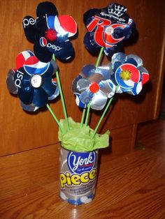 All Recycled flower arrangement.  Flower holder is a used rotal can  stems are old reed diffusers  and the middles are all stuff from the junk drawer ;)  oh ya and the flowers are soda cans