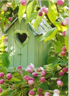 This cute little birdhouse blends right in with the flowers & leaves.  Like the heart opening!
